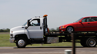 Tow truck with red car